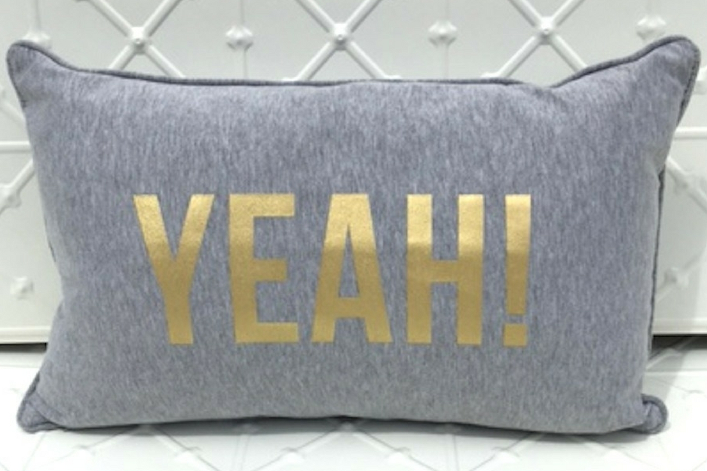 Cushion with 'YEAH' printed in gold, indicating style of textiles for wedding and event hire.